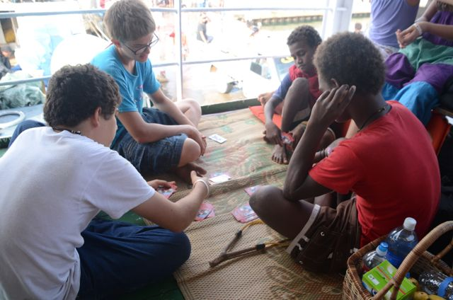 the Choate kids and their friends playing cards while they wait for the ship to depart